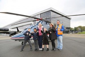 family photographed infront of helicopter